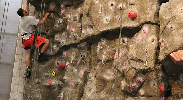 Young man climbing a rock wall.