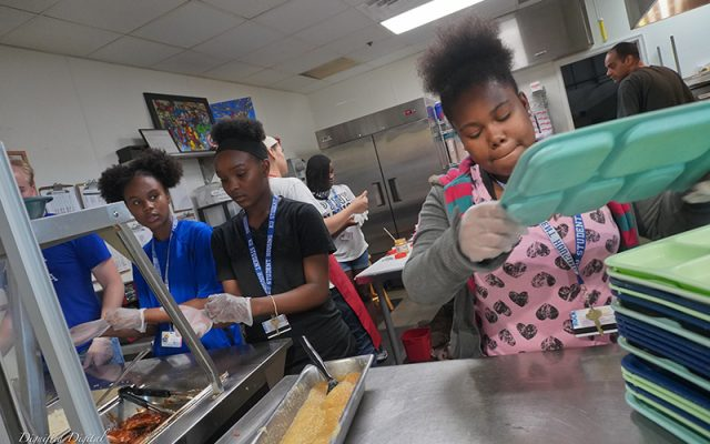 Three girls helping prepare lunches.